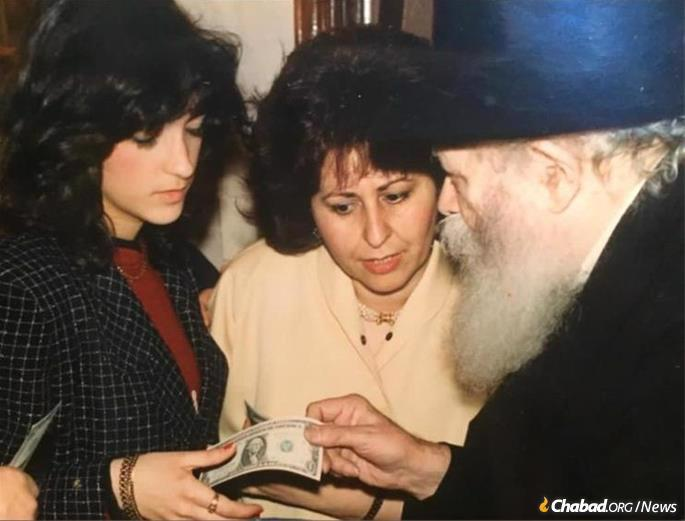 Bentolila (left) and her mother, Rebbetzin Rachel Hadad, receive a dollar and a blessing from the Rebbe. Bentolila never sought the limelight, firm in her belief that the only one who needed to be appraised of her work was the Rebbe. (Credit: Bentolila family/JEM)