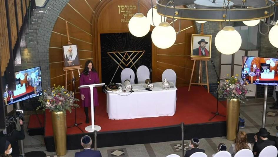 """Sterni Wolff speaks at the grand opening of the Chabad Center in Hanover, Germany, called """"Haus Benjamin,"""" or """"Binyamin's House,"""" in honor of her late husband, Rabbi Binyamin Wolff."""