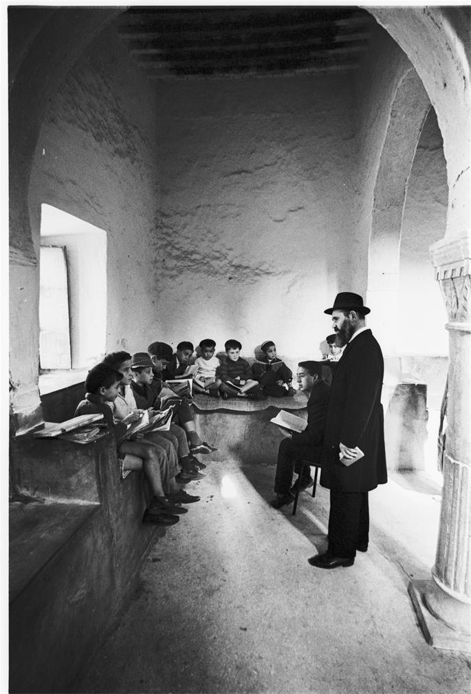 Rabbi Nissan Pinson, a pioneering figure in Jewish education in Tunisia, hears some young students recite their lessons at the yeshiva in Djerba, Tunisia (credit: 