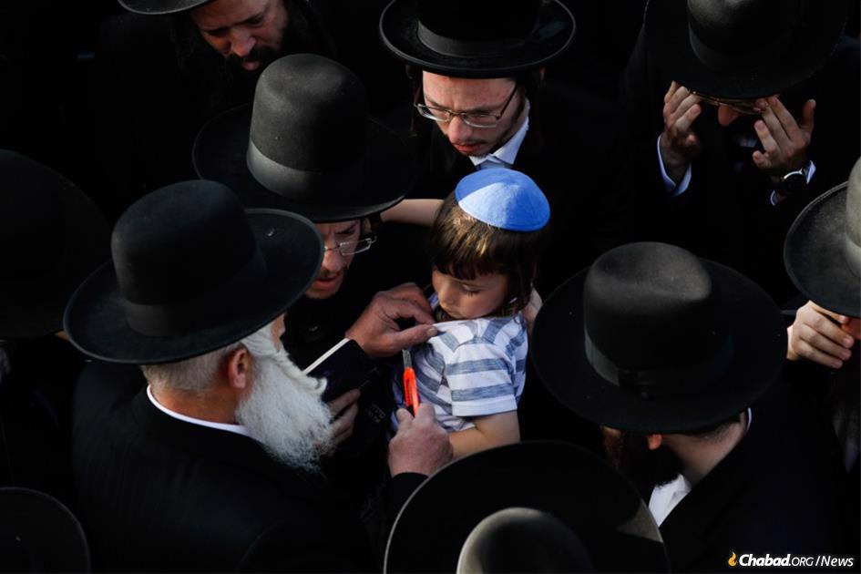 At his father's funeral, an orphan has his garment ritually torn by a rabbi as a sign of mourning. The boy's father died on April 30, along with 44 others worshippers during Lag BaOmer celebrations in Meron, Israel. (Photo: Oliver Fitousi/Flash90)