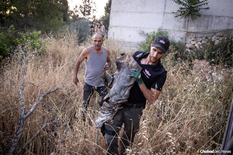 Residents of Moshav Beit Nekofa, outside Jerusalem, look on as Israeli police sappers remove the remains of a rocket fired from the Gaza Strip that fell near their homes. (Photo by Yonatan Sindel/Flash90)