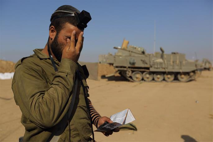 An Israeli soldier near the Israeli border with Gaza, on July 31, 2014. Following the Rebbe's call in 1967, thousands of Jewish men and boys have put on tefillin and prayed for the safety and survival of the Jewish nation (photo: Yaakov Naumi/FLASH90).
