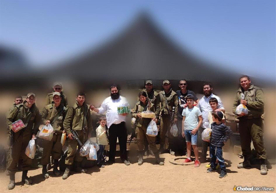 Rabbi Asher Pizam, along with his children and volunteers from Chabad of Sderot, brought soft drinks and chips to IDF troops. (Photo altered by military censor)