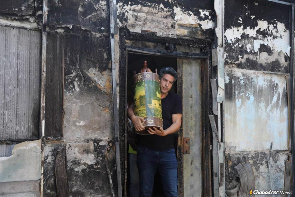 In Lod, Israel, a congregant carries a Torah scroll from his torched synagogue. In support of and in solidarity with their brothers and sisters in the Holy Land, Jewish men, women and children from around the world will gather in synagogue on Monday, May 17, for the annual reading of the Ten Commandments on the first day of the holiday of Shavuot, just as they stood as one people 3,333 years ago at Mount Sinai. (Photo: Yonatan Sindel/Flash90)