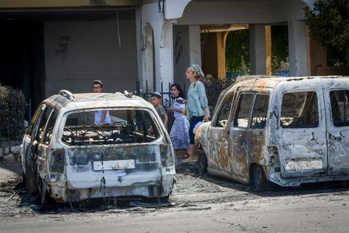 A Jewish famly passes by torched synagogues, cars and vandalized stores in the central Israeli city of Lod, following a night of heavy rioting by Arab residents in the city. (Photo: Avshalom Sassoni/Flash90)