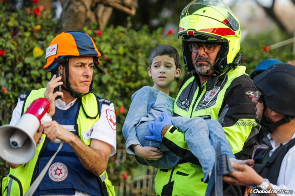 In Ashkelon, an emergency service worker carries 8-years-old Eitan Vhnstok from his apartment building after it was hit by a rocket fired from Gaza. (Photo: Edi Israel/Flash90)