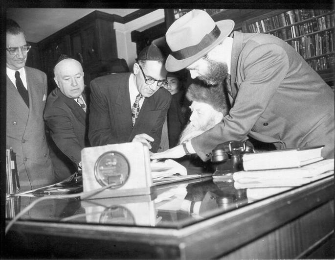 The Rebbe, Rabbi Menachem M. Schneerson, of righteous memory, helps his father-in-law during the latter's United States citizenship ceremony at 770 Eastern Parkway, in the Crown Heights section of Brooklyn, New York