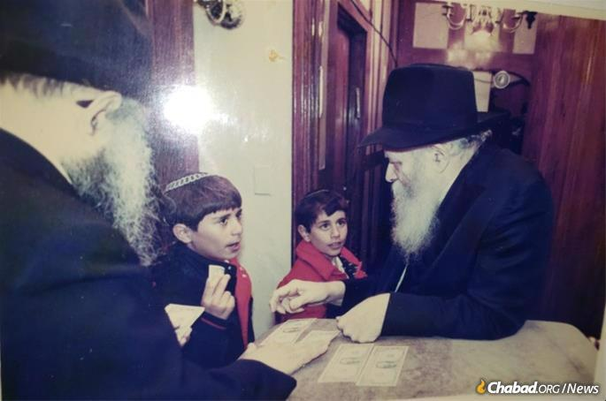 Two of Haller's grandchildren receive a dollar and a blessing from the Rebbe.