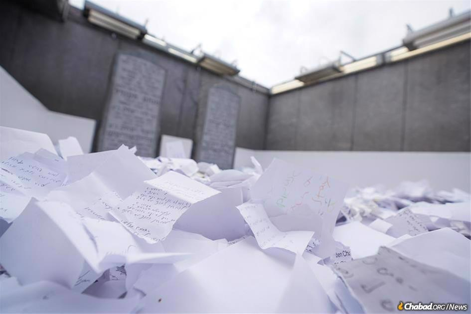 The anniversary of passing, 3 Tammuz, is traditionally a day spent in reflection, learning, prayer, and above all, positive action. One key observance is writing a letter to be placed at the Ohel for the Rebbe's guidance and intervention On High in the age-old tradition of written prayer petitions at our holiest sites. (File photo: Bentzi Sasson)