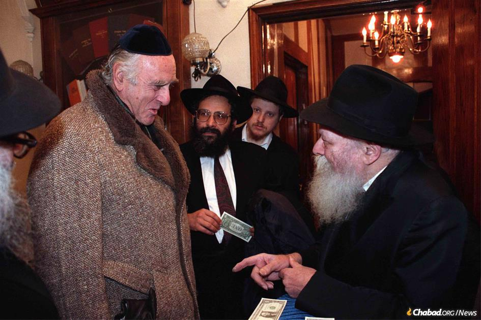 Judge Jack B. Weinstein receives a dollar and a blessing from the Rebbe, Rabbi Menachem M. Schneerson, on Dec. 17, 1989, as Rabbi Sholom Lipskar looks on. Weinstein passed away on June 15, 2021. (Photo: Jewish Educational Media/The Living Archive)