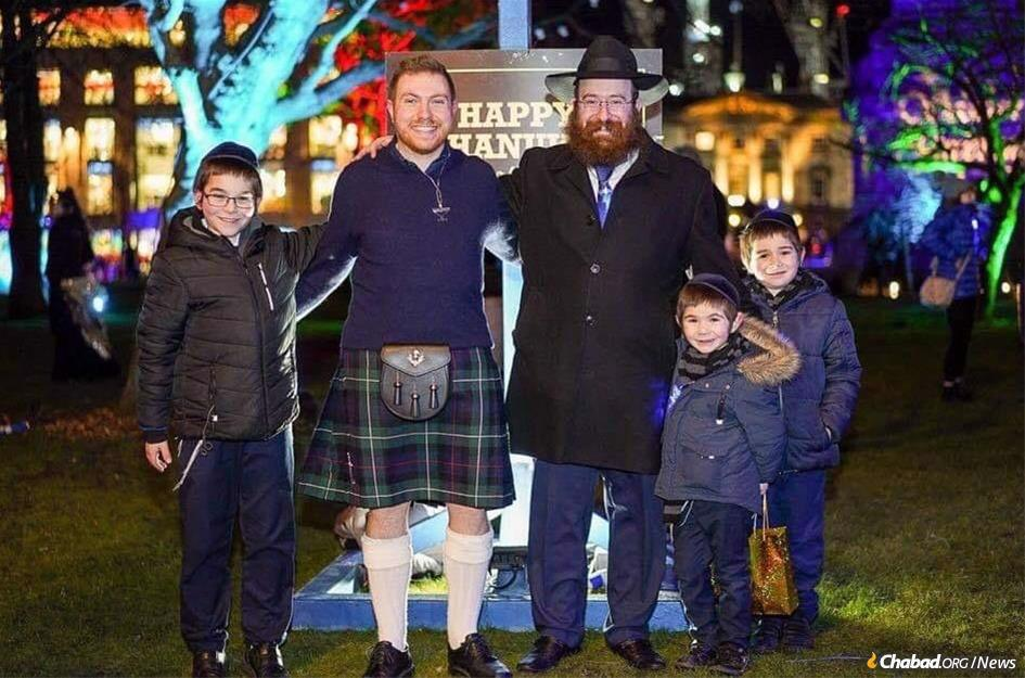 Adam Schwartz, a student at the University of Edinburgh, with Rabbi Pinny Weinman and children last Chanukah.