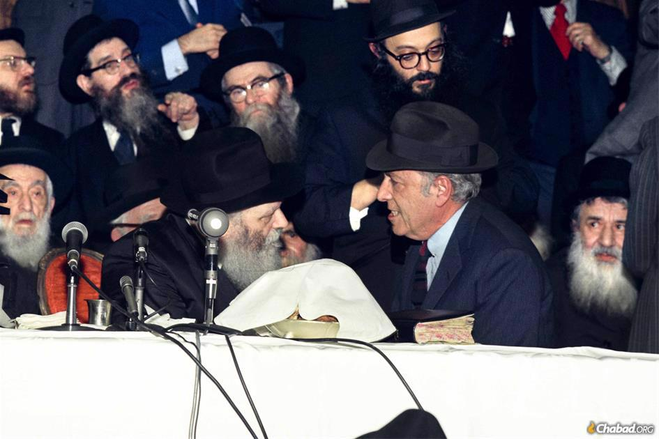 Herman Wouk drew deeply from his intense, decades-long relationship with the Rebbe, Rabbi Menachem M. Schneerson, of righteous memory, shown together here at a Chassidic gathering in 1975. (Photo: Velvel Schildkraut via The Living Archive/Jewish Educational Media)