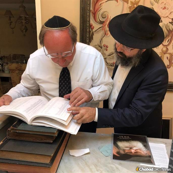Holtz (left) and Berkowitz look through records. The magazine with the Rebbe's image on the cover lies on the counter.