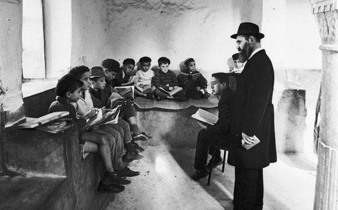 Rabbi Nissan Pinson, a pioneering Chabad activist in Tunisia, hears some young students recite their lessons at the yeshiva in Djerba, Tunisia (credit: Jean Mohr/JDC).