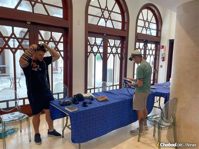 Two men don tefillin at the Shul of Bal Harbour, Fla., as the community continues to wait for news and hold out for a miracle.
