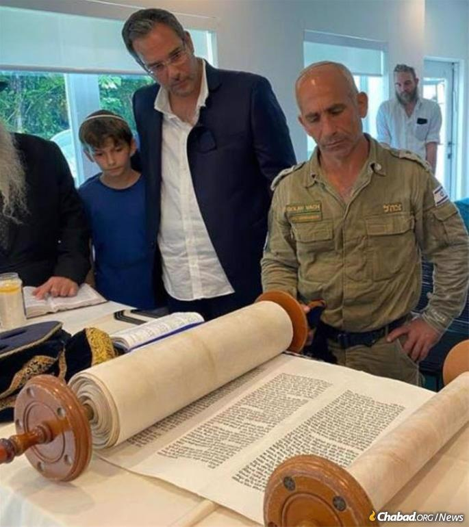 IDF Col. Golan Vach receives an aliyah to the Torah, as Dovy Ainsworth, center, and other family members look on.