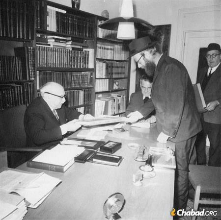 1967: Rabbi Adin Steinsaltz presents a new volume of his revolutionary edition of the Talmud to President Zalman Shazar, with Knesset Speaker Kadish Luz (seated, center) looking on. In the background is Mr. Avraham Steinsaltz, who had by then taken an administrative role in the Isreali Institute for Talmudic Publications.