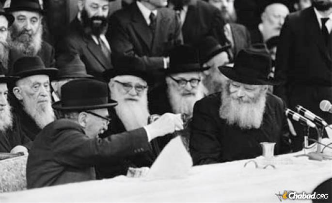 """On one of his many visits to the Rebbe, Israel's President Zalman Shazar participates in a farbrengen and raises his glass to the Rebbe. Shazar was a participant in the """"Chein Circle"""" class taught by Steinsaltz from circa 1960 onward, and would become a key supporter of his project to make the Talmud accessible to all."""