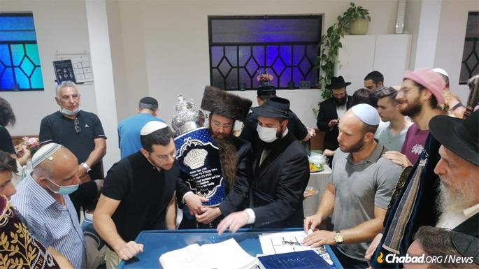 """Rabbi Moshe Naiditch of Jerusalem holds the Torah scroll at the siyum, or """"completion,"""" of the writing of the Torah scroll as his brother, Rabbi Eli Naiditch, looks on. The scroll dedicated by their family in honor of their late father, David Naiditch. (Photo: Avi Noo)"""