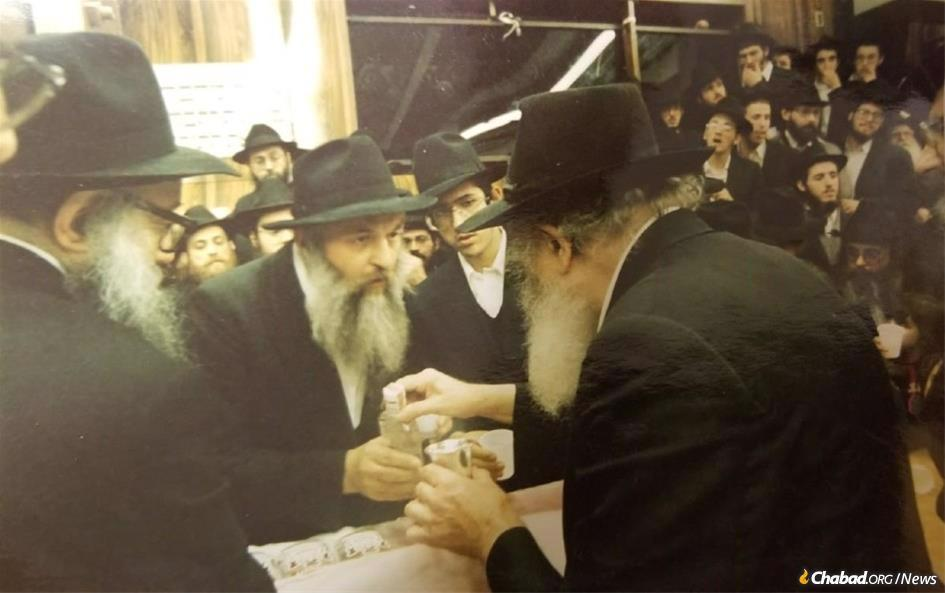 Rabbi Mendel Aronow receives a bottle of 'mashke' from the Rebbe for the Toronto Jewish community at the conclusion of a farbrengen.