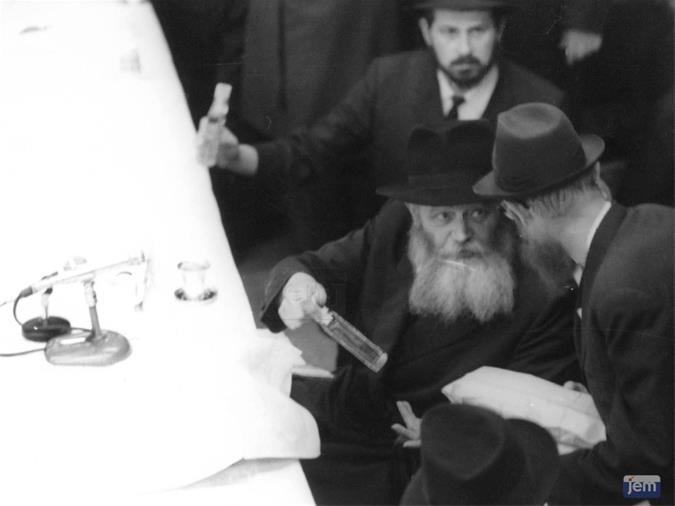 """In Shvat 5730, January 1970, Adin Steinsaltz made his first visit to New York as President Zalman Shazar's personal representative to the Rebbe. Here Steinsaltz, right, approaches the Rebbe to receive a small bottle of vodka. He also was received in a private audience by the Rebbe, who subsequently wrote of him """"I found in him qualities that are even greater than what was told to me and written to me."""""""