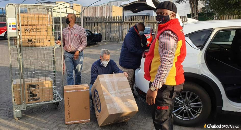 Workers at RAM Couriers in Johannesburg prepare shipments of provisions to be airlifted to Jewish communities impacted by the dual crisis of riots and pandemic.