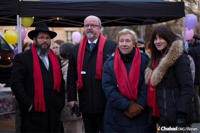 Rabbi Binyomin and Shterna Wolff at the public menorah lighting at the Opera Square in Hanover with the Hanover police chief and his wife.