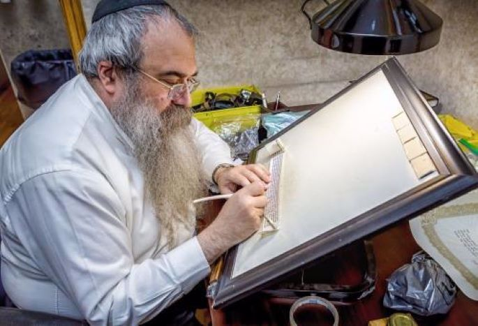 A scribe at work, checking a tefillin parchment (Photo: Eliyahu Parpya)