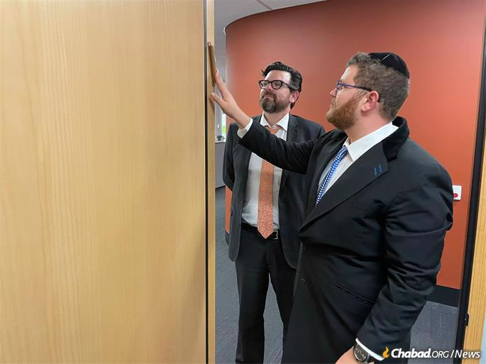Rabbi Daniel Lieberman of the Perth Hebrew Congregation affixes a mezuzah to the doopost of Justice Solomon's chambers as Chief Justice Quinlan looks on.