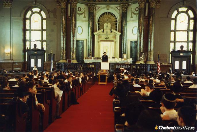 Oholei Torah yeshiva boys in the massive former sanctuary of the Brooklyn Jewish Center. As part of an expansion the sanctuary was transformed into two floors of classrooms and a study hall in 2001. (Credit: Oholei Torah)
