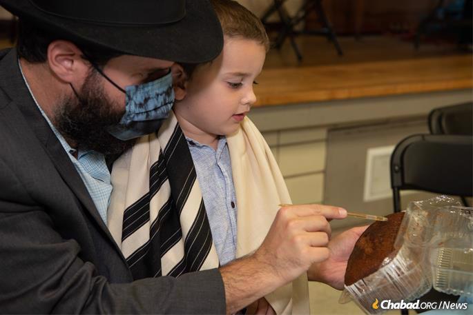Rabbi Eliezer and Zevi Zalmanov read aloud from a Hebrew passage embossed on a sweet honey cake (Photo: Leah Boyarskiy).