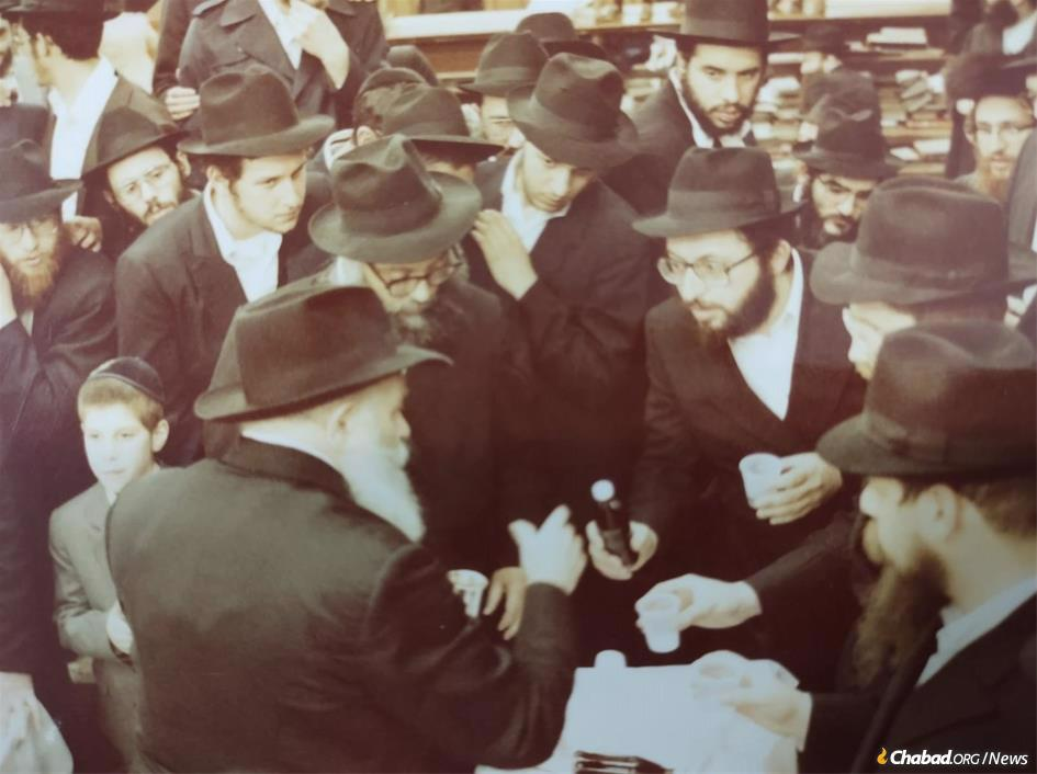 The Rebbe would often give Rabbi Sholom Jacobson symbolic bottles of wine or spirits, demonstrating his personal encouragement of his work. This picture was taken in 1984.