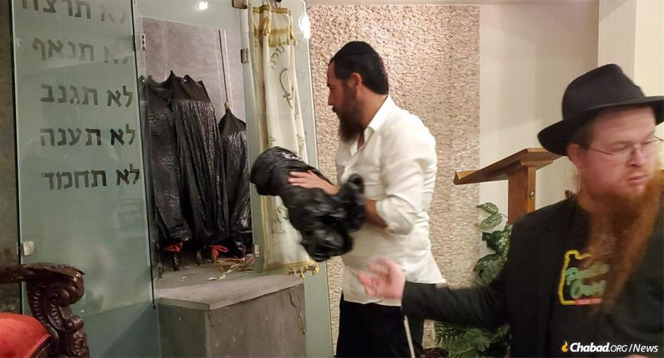Volunteers at the Chabad Center of Metairie safeguard the Torah scrolls as Hurricane Ida approaches.
