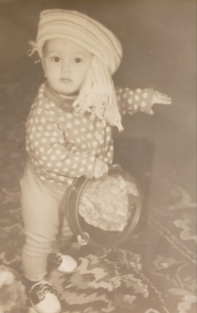 As a child in Soviet Union playing dress up, holding a tambourine.