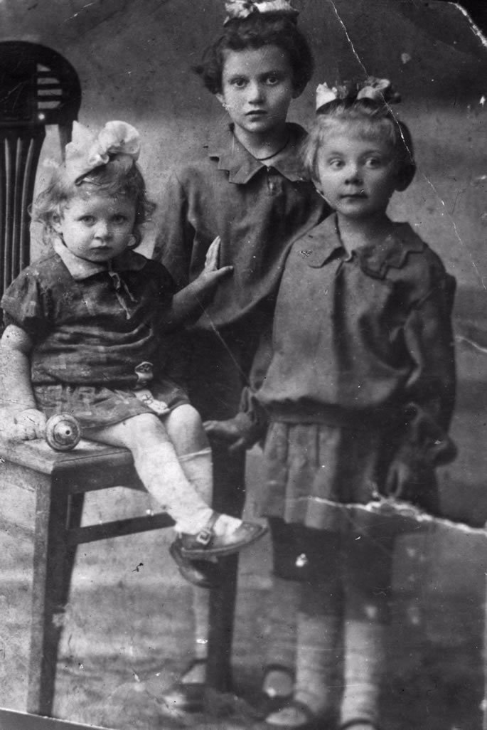 Zelda, standing on the right with her two sisters: Rachel, the oldest, next to her and baby, Olga, sitting down.