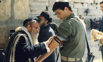 Rabbi Moshe Weber helps a Jew put on tefillin at the Western Wall