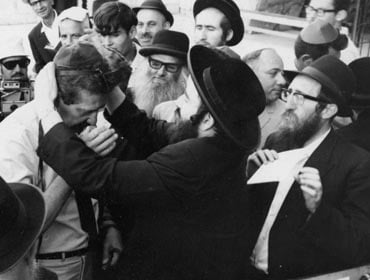 Major General Ezer Weizmann, Chief of Operations of the IDF puts on tefillin at the Western Wall.