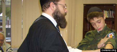 Oleg Tkacha puts on tefillin during his Bar Mitzvah celebration.
