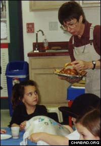 Robin Schneiderman hands out challah to her preschoolers during a Friday-afternoon Shabbat party.