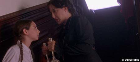 """Played by Judy Winegard, right, Miss Agatha Grimshaw takes away the Shabbat candles belonging to Miriam Aronowitch, played by Abby Shapiro in the new movie """"A Light for Greytowers."""""""