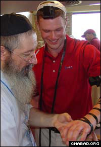 Rabbi Tzvi Lipinsky helps, open golf gold medal winner, David Merkow, put on tefillin at the 11th Pan-American Maccabean Games in Buenos Aires, Argentina.