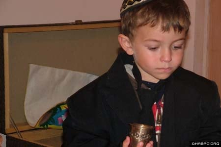 Wearing a jacket and a tie, a young boy makes Kiddush by reciting a blessing over a cup of grape juice in his right hand.