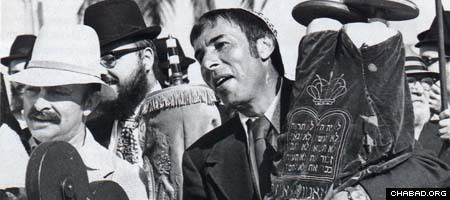 Businessman Mel Landow dances with a Torah scroll at the 1974 opening of the new Landow Yeshivah Center.