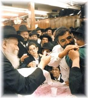 Le Rabbi de Loubavitch coupant la première mèche d'un petit garçon de trois ans