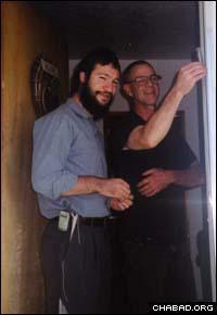 Chabad-Lubavitch Rabbi Zalman Mendelsohn helps a Jewish resident of Wyoming affix a mezuzah to his doorpost.