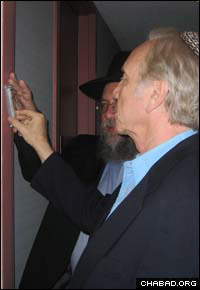 Accompanied by Rabbi Yisrael Deren, co-director of Chabad-Lubavitch of Fairfield County, Connecticut Sen. Joseph Lieberman affixes a mezuzah to his new home in Stamford.