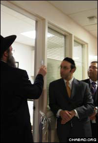 Rabbi Zalman Wolowik, co-director of Chabad-Lubavitch of the Five Towns, affixes a mezuzah to a new Shabbat suite at S. Francis Hospital in Roslyn, N.Y.
