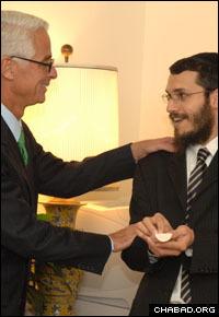 Rabbi Shneur Zalman Oirechman, right, explains the meaning of the mezuzah to Florida Gov. Charlie Crist.