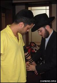 Rabbi Yehoshua Kaminetzky, the new co-director of Chabad-Lubavitch of Serbia, helps a member of the local Jewish community in Belgrade don tefillin.
