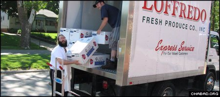 Rabbi Yossi Jacobson, director of Chabad-Lubavitch of Iowa, unloads produce contributed by a local company to help feed flood victims.